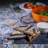 Anchovies on rye toasts with tomato salad